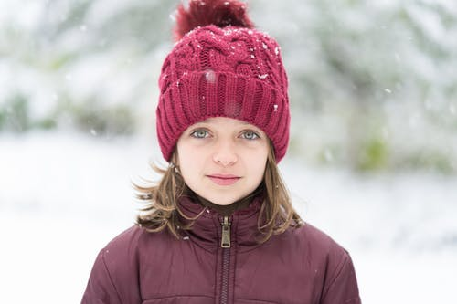 Calm young girl with short brown hair and light eyes in winter down jacket and hat with pompom standing on street with falling snowflakes in winter park