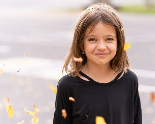 Happy girl in autumn foliage