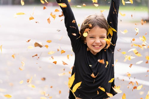 Smiling young girl with brown hair in casual clothes standing with hands up in sunny street with falling autumn leaves