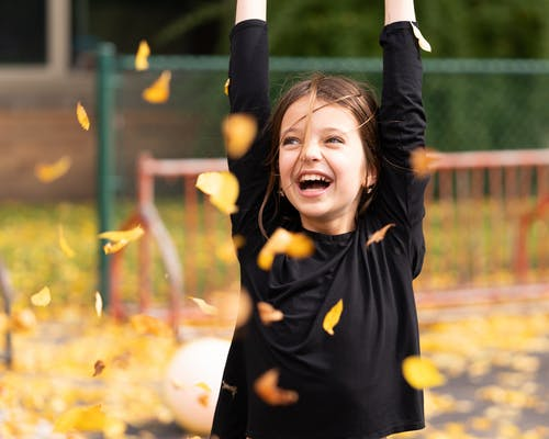 Joyful girl playing with foliage