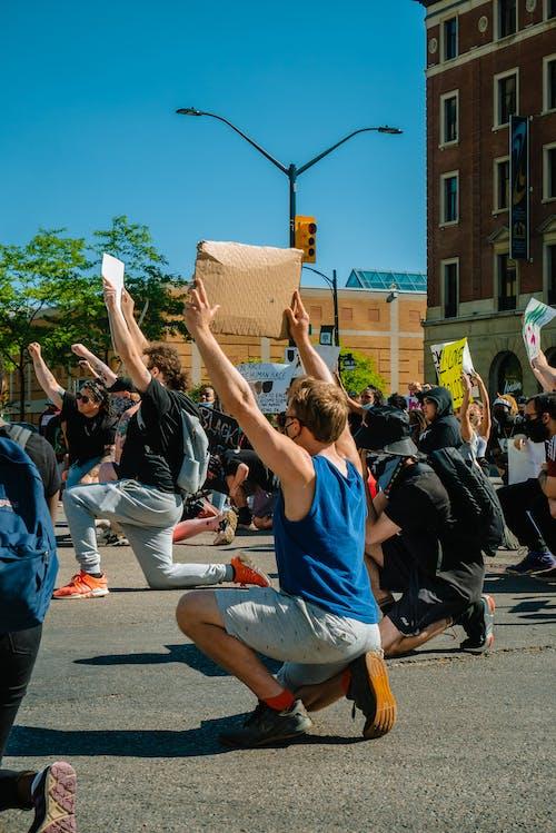 Photo of People Kneeling on Street While Holding Cardboard