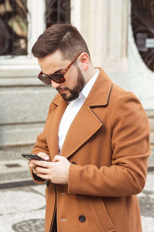 Man in Brown Suit Jacket Holding Smartphone