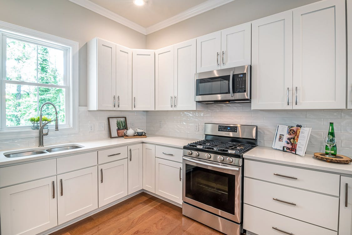 White Wooden Kitchen Cabinet and Black Microwave Oven