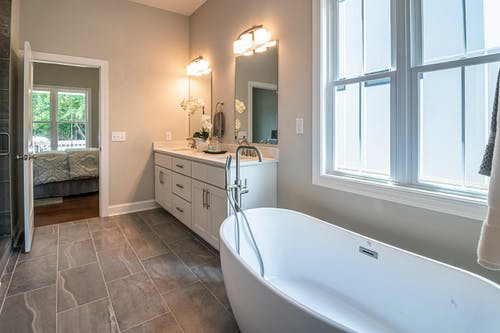 White Bathtub Near White Wooden Framed Glass Window
