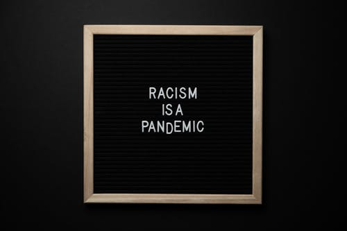 Phrase Racism Is Pandemic on signboard