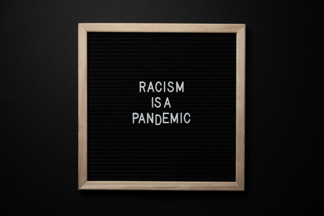 Overhead view of slogan Racism Is Pandemic on black square signboard in light of lamps on black background