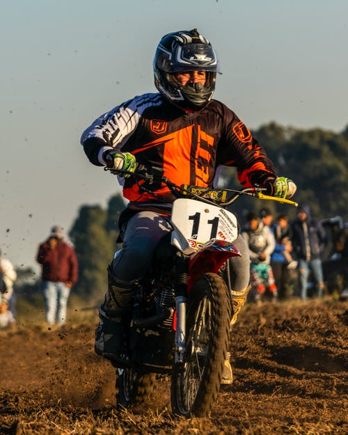 Man in Red and Black Motorcycle Suit Riding Motocross Dirt Bike