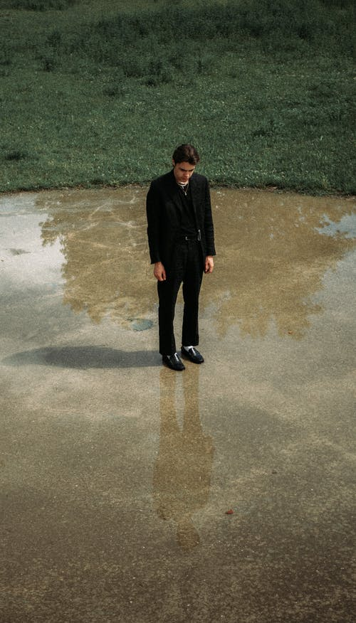 Melancholic man in suit standing on wet ground in park