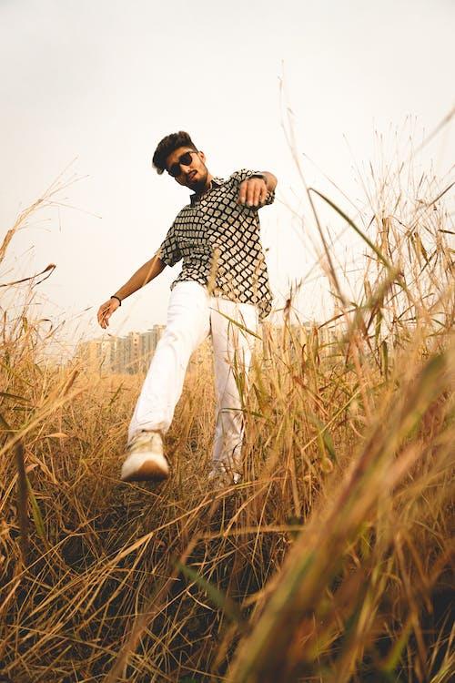 Stylish man walking in grassy meadow
