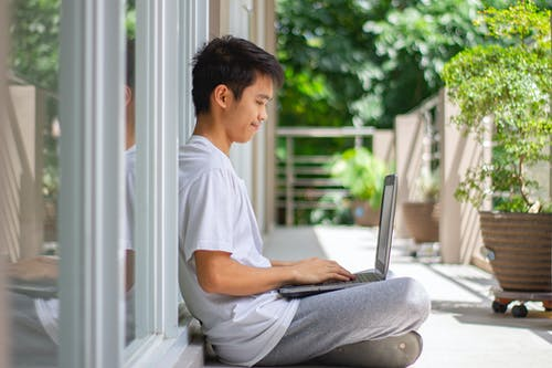 Young Man Sitting on the Floor and Using a Laptop