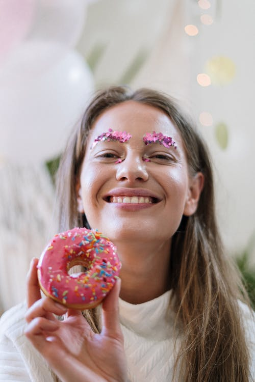 Woman in White Crew Neck Shirt With Doughnut on Her Face