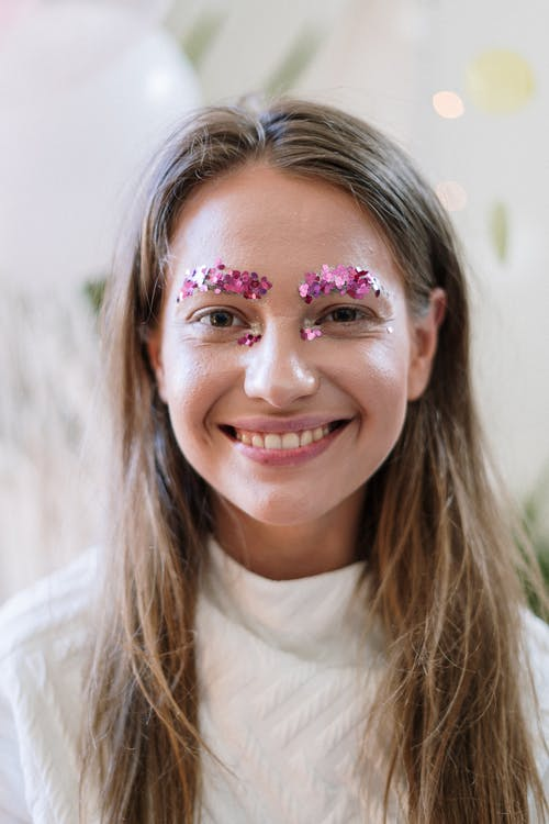 Woman in White Crew Neck Shirt With Pink and White Floral Face Paint