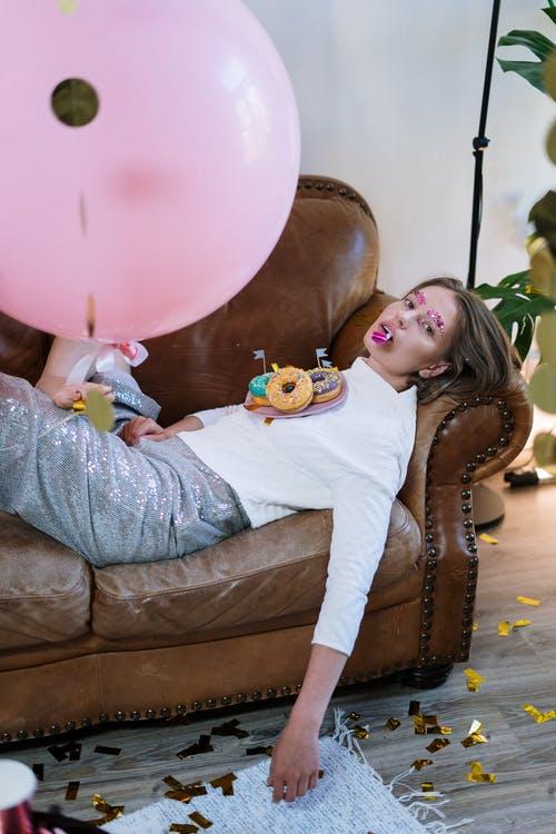 Girl in White Long Sleeve Shirt and Gray Pants Sitting on Brown Leather Couch