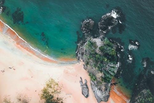 Rocky formations in ocean water washing sandy shore