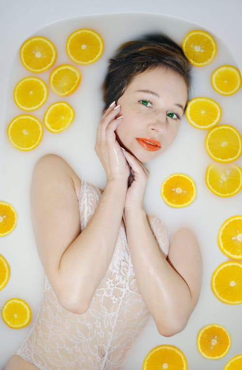 Content woman in bath with oranges