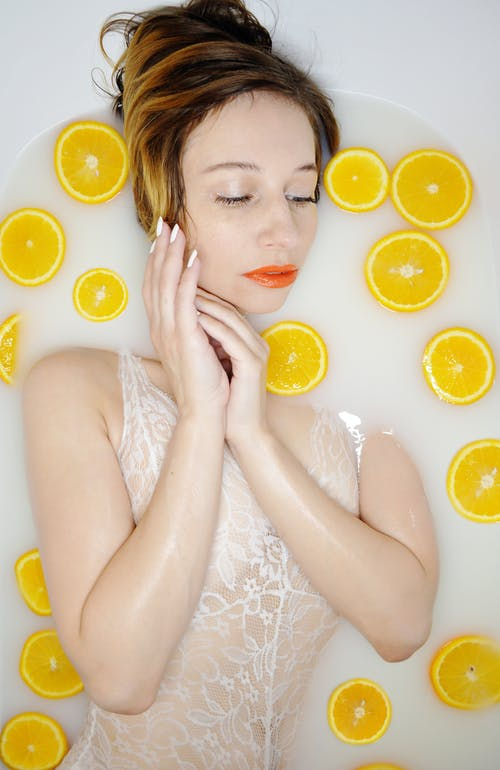 Serene woman lying in bath with slices of orange