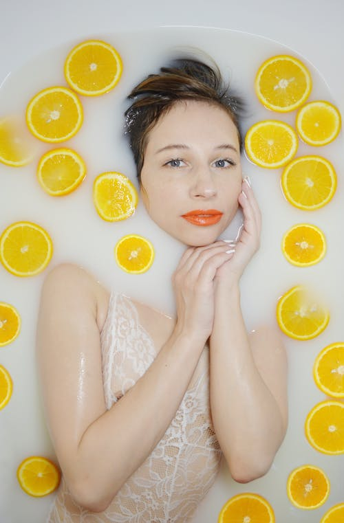 Top view of peaceful female in bodysuit looking at camera while lying in bathtub with orange slices during hygiene routine