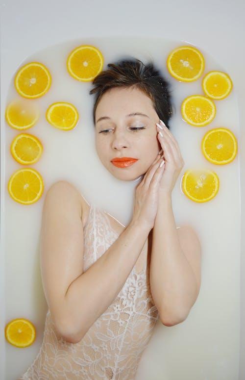 Tranquil woman in bodysuit lying in bath with milk water