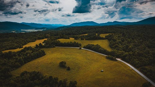 Drone view of wavy roadway between grass meadows with woods behind mounts under cloudy sky