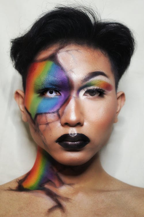 Young creative man with colorful creepy makeup with dark lips and lenses in eyes