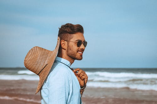 Side view of cheerful young male tourist in stylish straw hat and sunglasses smiling and admiring waving ocean during summer holidays