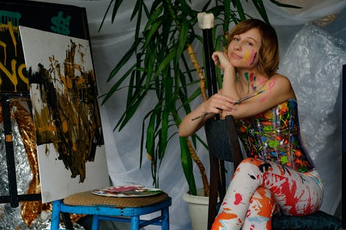Positive messy female artist with paintbrush looking at camera while sitting near painting and palette of paints in art studio