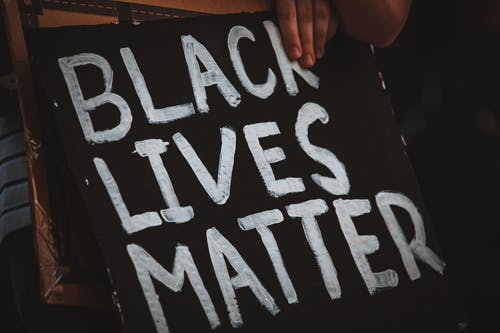 Crop protester near placard with Black Lives Matter title