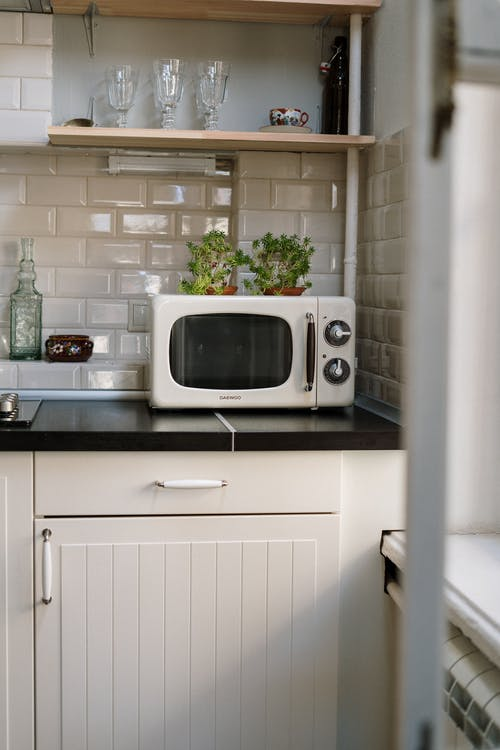 Silver Microwave Oven on White Wooden Cabinet