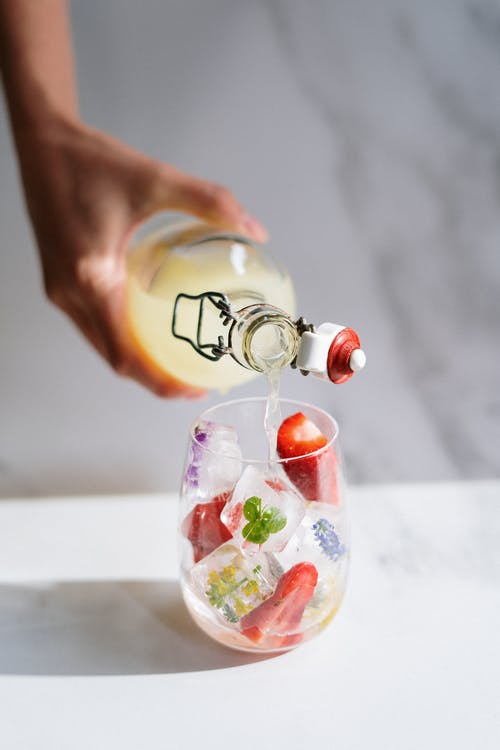 Person Holding Clear Glass Bottle With Red and White Ribbon