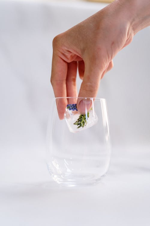 Person Holding Clear Drinking Glass With Ice