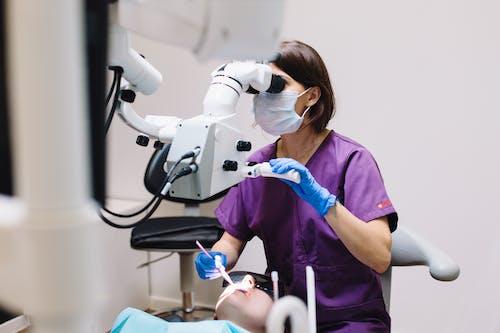 Woman in Purple Shirt Using White Robot