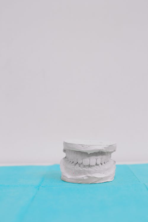 White and Gray Ceramic Jar on Blue Textile