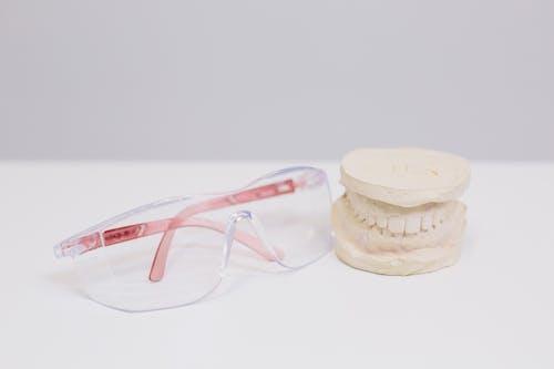 Red Framed Eyeglasses Beside White Plastic Container