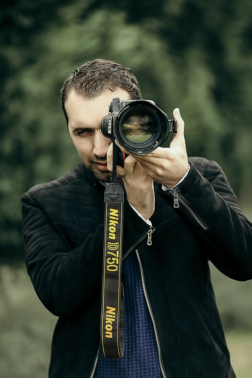 Concentrated male photographer in casual clothes looking through objective lens of camera while taking photo on nature with blurred background