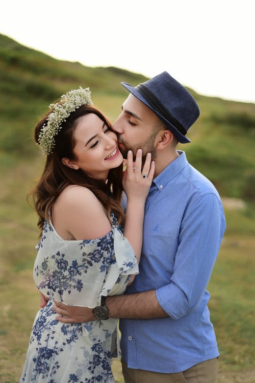 Tender man in hat kissing charming woman with wreath on cheek while hugging on grassy meadow in daylight in nature