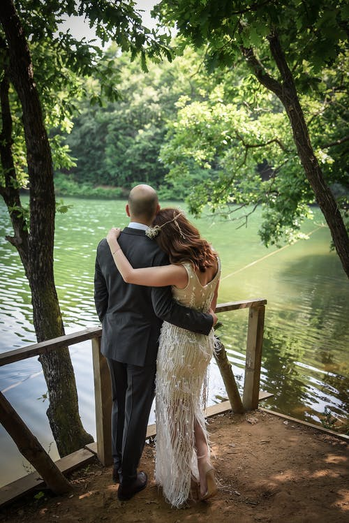 Back view of unrecognizable loving couple hugging on boardwalk near calm lake amidst green trees in sunlight in summer day