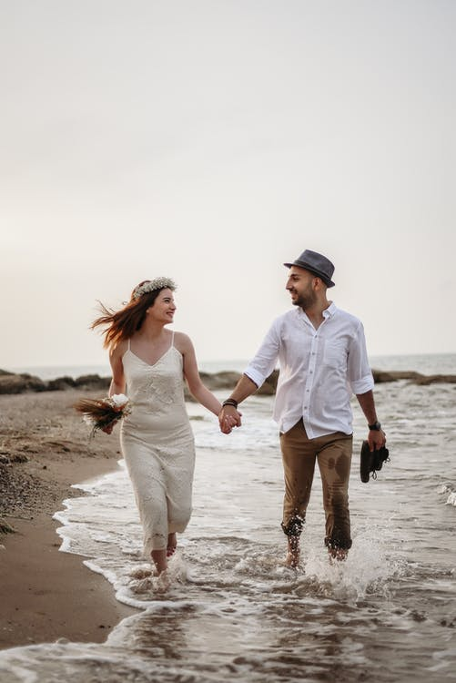 Loving couple in white clothes and headdresses running on coastline in summertime against gray sky and looking at each other while holding hands