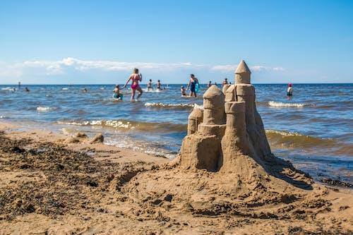 Sandcastle built on sunny beach near waving sea
