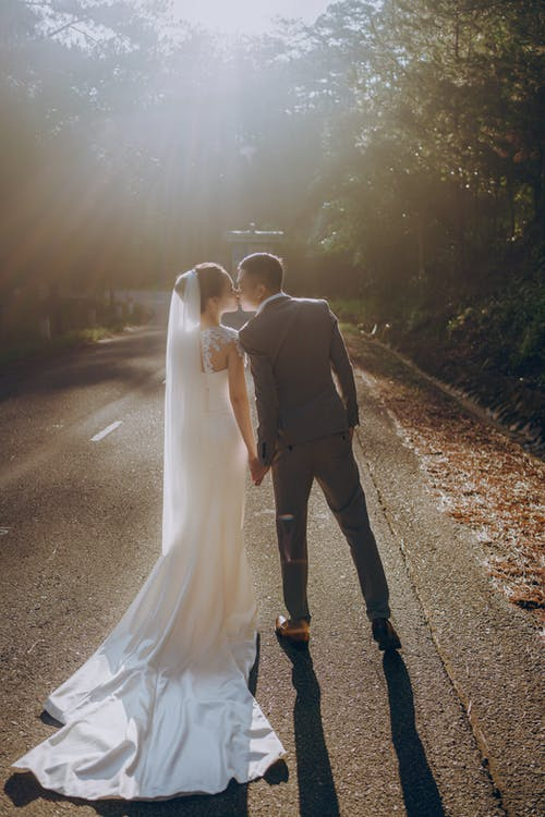 Back view of anonymous bride and groom in wedding outfits kissing and holding hands while standing on walkway among trees