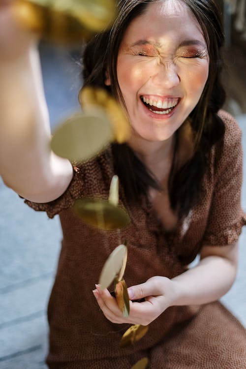Smiling Woman in Brown and White Long Sleeve Shirt Holding Brown Wooden Spoon