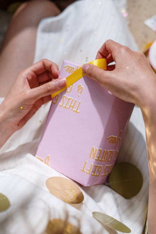 Person Holding Yellow and Pink Labeled Bottle