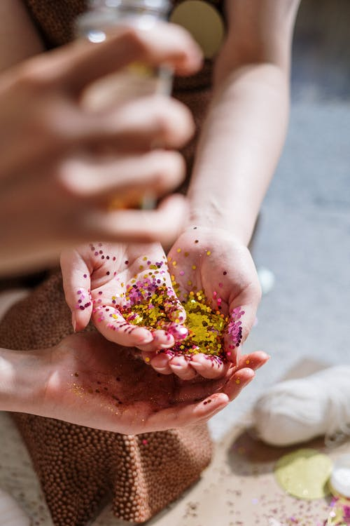Person Holding Pink and White Flower Petals