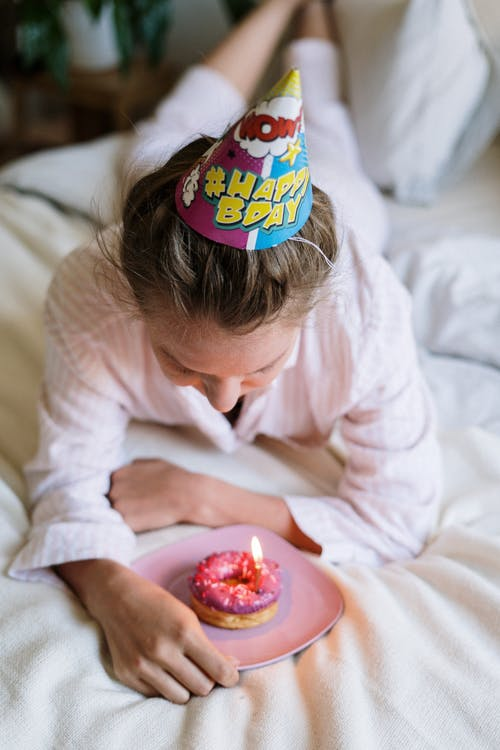 Girl in White Long Sleeve Shirt Eating Pink Cake