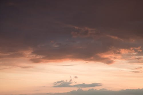 From below of fluffy gray clouds floating on colorful orange sky at sundown
