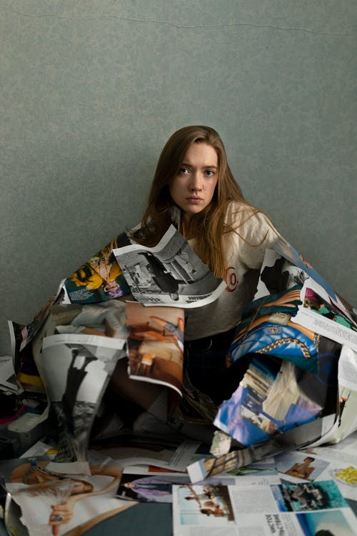 Woman with torn out pages sitting on floor