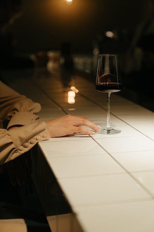 Persoon In Bruine Jas Met Helder Wijnglas
