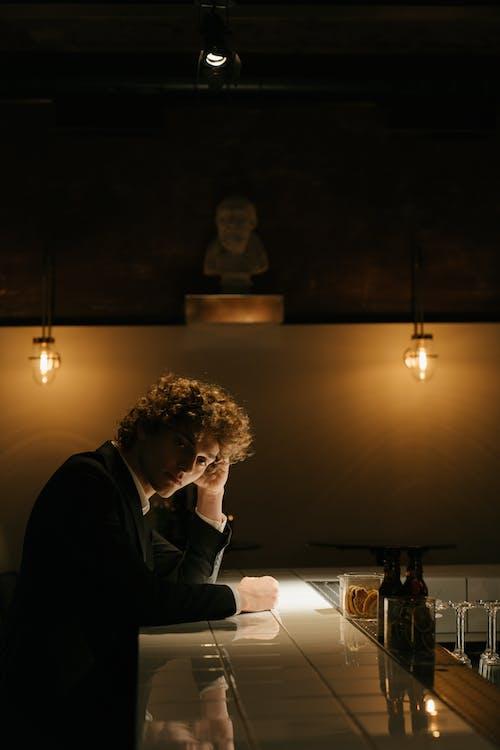 Мужчина в черном пиджаке сидит за столом