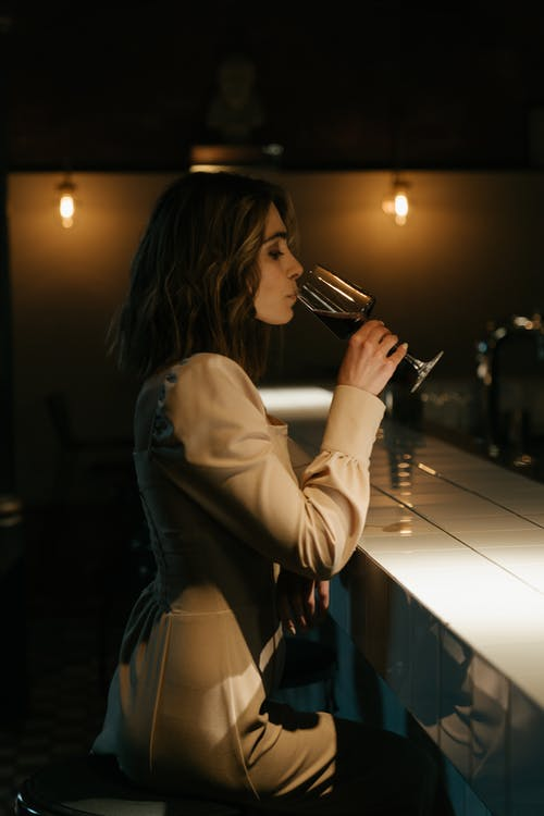 Woman in White Long Sleeve Shirt Drinking from a Glass