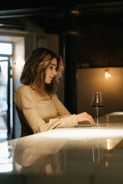 Женщина в коричневой рубашке с длинным рукавом сидит за столом