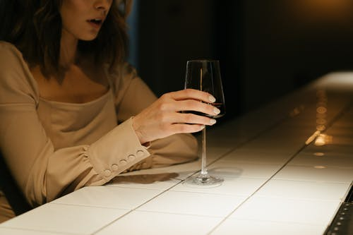 Woman in Brown Long Sleeve Shirt Holding Clear Wine Glass